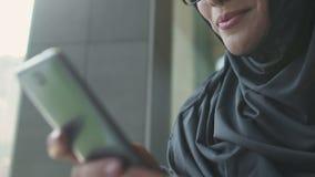 Messaggio musulmano della lettura della donna dal ragazzo sul telefono, informante a datare sito stock footage