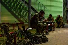 Messaggio serio di scrittura del soldato di vista laterale in telefono mentre durando in uniforme e circondato dalle armi tecnolo immagini stock