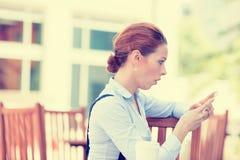 Messaggio sorpreso della lettura della donna sul suo Smart Phone Fotografie Stock Libere da Diritti