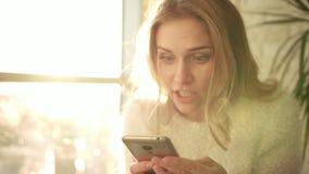 Messaggio sorpreso della lettura della donna sul telefono Ragazza allegra con il fronte sorpreso stock footage