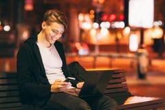 Messaggio sorridente della lettura del tipo sullo smartphone Fotografia Stock Libera da Diritti
