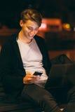 Messaggio sorridente della lettura del tipo sullo smartphone Fotografia Stock