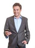 Messaggio sorridente di scrittura dell'uomo d'affari sul telefono Fotografie Stock Libere da Diritti