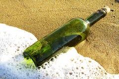 Messaggio in una bottiglia di vetro in una spiaggia Fotografia Stock