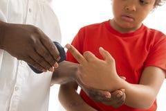 Messen Sie die Anwendung des kleinen Jungen des Kinderglukoseniveau-Blutprobe-Diabetes stockbild