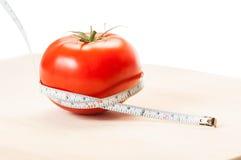 Messen Sie Kalorien einer roten Tomate mit einem Zentimeter Nähren Sie Konzept Stockbild