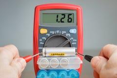 Messende Batteriespannung mit Vielfachmessgerät Stockbilder