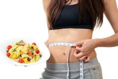 Messende Taille der Frau und Anhalten der Diätnahrung Stockbilder