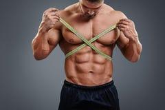 Messende Taille des Bodybuilders mit Maßband Stockbild