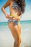 Messende Taille des hübschen Brunette am Strand Lizenzfreie Stockfotos