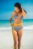 Messende Taille des hübschen Brunette am Strand Lizenzfreies Stockfoto