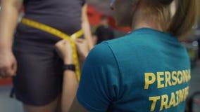 Messende Taille des persönlichen Trainers der beleibten Frau, Ergebnisse des Trainierens überprüfend stock video