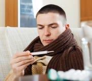Messende Temperatur des Mannes mit Thermometer Stockfotos