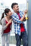 Messende Wände der jungen indonesischen Paare in der neuen Wohnung Lizenzfreies Stockbild