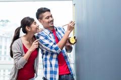 Messende Wände der jungen indonesischen Paare in der neuen Wohnung Lizenzfreies Stockfoto