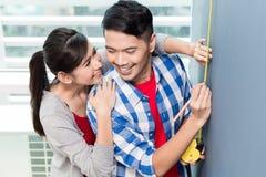 Messende Wände der jungen indonesischen Paare in der neuen Wohnung Stockfotos