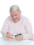 Messende waagerecht ausgerichtete Blutprobe der Glukose der älteren Frau des Diabetes Lizenzfreies Stockfoto