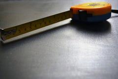 Messender Maßband auf schwarzem Hintergrund lizenzfreies stockbild