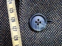 Messendes Band und geknöpfter Knopf auf Tweedjacke Stockfoto