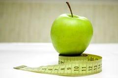 Messendes Band und grüner Apfel Stockfoto