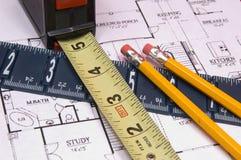 Messendes Band und Tabellierprogramm mit Bleistiften auf dem Haus floorplan Lizenzfreie Stockfotos