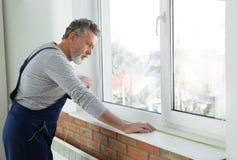 Messendes Fenster des Service-Mannes für Installation lizenzfreie stockfotografie