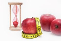 Messendes Metter mit roten Äpfeln und der Sand-Glasuhr, lokalisiert auf weißem Hintergrund Fetter Burning- und Gewichtsverlustpro Stockfotografie