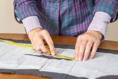 Messendes Schneidermuster der Damenschneiderin auf dem Tisch lizenzfreie stockbilder
