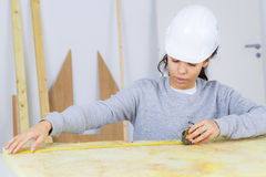 Messendes Sperrholz des weiblichen Tischlers Stockbild