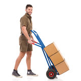 Messenger walking with a delivery cart Royalty Free Stock Photos