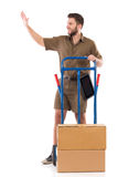 Messenger waving a hand. Cheerful delivery man waving a hand and looking away. Full length studio shot isolated on white Stock Images