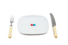 Messer, Bolzen und Platte mit den roten und blauen Tabletten Stockfoto