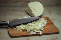 Messer, das den Kohl schneidet, um die faulen Kohlrollen oder -fleischklöschen zuzubereiten Stockfoto