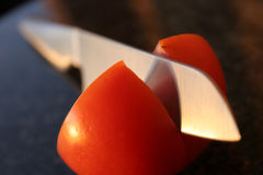Messer, das eine Tomate schneidet Stockfotografie