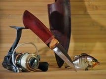 Messer für Reinigungsfische auf einem Hintergrund einer Angelrolle Stockfotografie