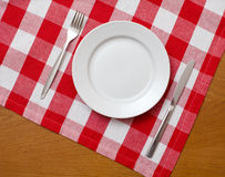 Messer, Platte und Gabel auf Tabelle mit roter Tischdecke Lizenzfreies Stockfoto