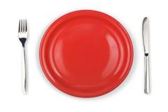 Messer, rote Platte und Gabel getrennt Lizenzfreies Stockfoto