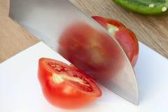 Messer schneidet die Tomate Stockfoto
