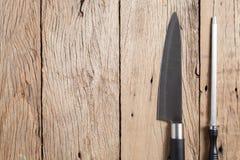Messer und Bleistiftspitzer auf altem Holztischhintergrund Stockfotografie