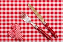 Messer und Fort mit rotem kariertem Herzen und Bogen Stockfotos