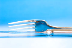 Messer und Gabel auf blauem Hintergrund Stockfotografie
