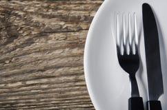 Messer und Gabel auf einer Platte Lizenzfreies Stockfoto