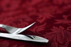 Messer und Gabel auf rotem Damast Lizenzfreie Stockfotografie