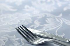 Messer und Gabel auf weißem Leinen Lizenzfreie Stockfotos