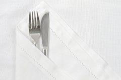 Messer und Gabel mit weißer Leinenserviette Stockfotografie