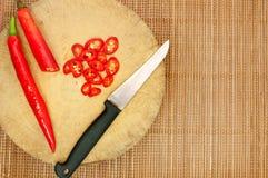 Messer und rote Paprikas Stockfotos