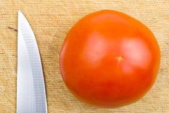Messer und Tomate auf einem hackenden Vorstand Lizenzfreies Stockbild
