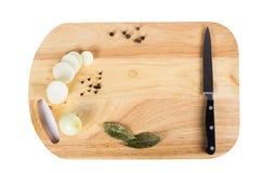 Messer und Zwiebeln, Gewürze auf einem Schneidebrett Lizenzfreie Stockbilder