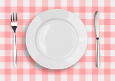 Messer, weiße Platte und Gabel auf dem Rot überprüft Lizenzfreie Stockfotos