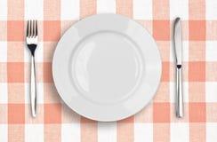 Messer, weiße Platte und Gabel auf rosafarbener Tischdecke Stockfotografie